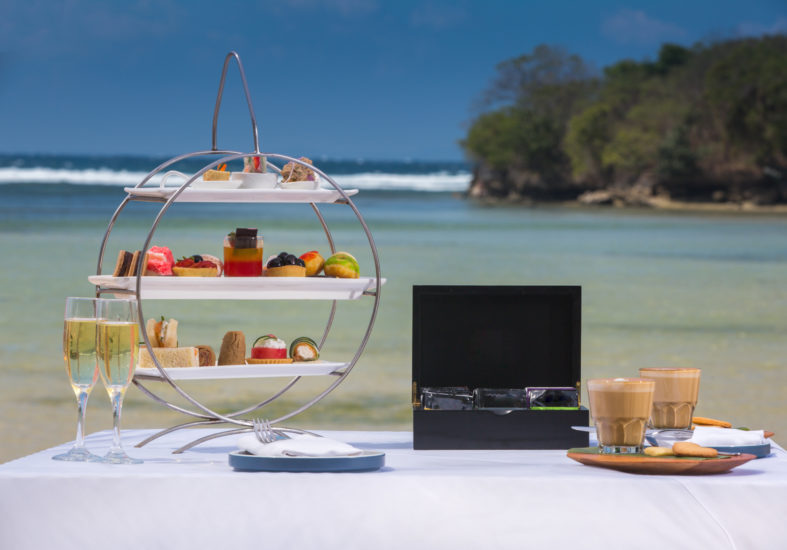 Afternoon tea set arrangement on beach, tea set with desserts, cookie, pastries ocean view